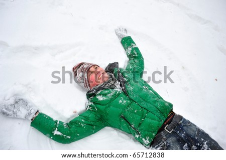 Portrait of young handsome man playing snowballs in winter park near tree wearing sportswear. laying on the ground - stock photo