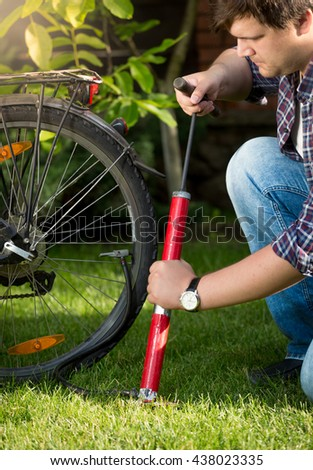 Portrait of young handsome man pumping bicycle tires at park