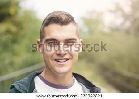 Portrait Of Young Handsome Man Smiling Outdoor - stock photo