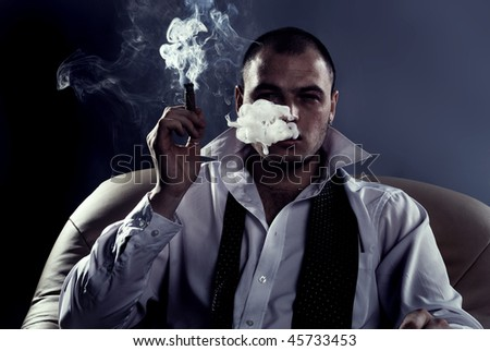 portrait of young handsome man smoking cigar - stock photo