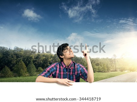 Portrait of young handsome man with blank banner pointing with finger up - stock photo