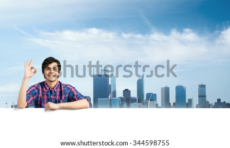 Portrait of young handsome man with blank banner showing ok gesture - stock photo