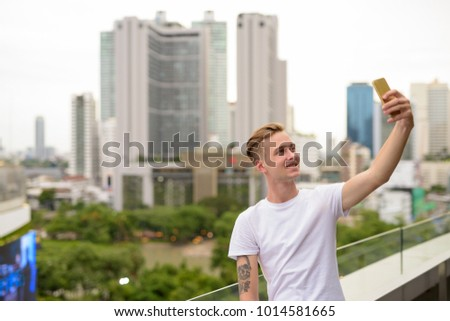 Portrait of young handsome man with blond hair against view of the city in Bangkok, Thailand