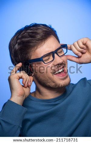 Portrait of young handsome man with headphones. handsome guy standing on blue background  - stock photo