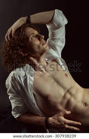 Portrait of young handsome man with open white shirt and rich curly hair over black background. Image toned. - stock photo