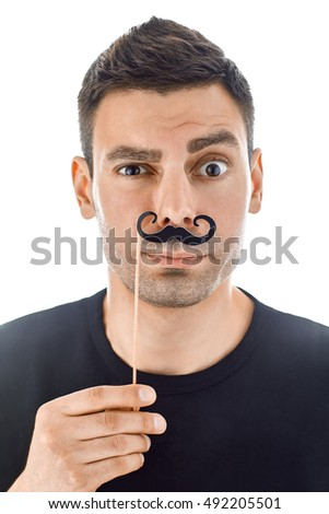 Portrait of young handsome man with paper moustaches making faces isolated on white background