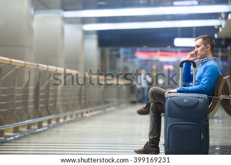 Portrait of young handsome person wearing casual style clothes sitting on the bench in modern airport terminal. Traveler making call using smartphone. Man travelling with luggage bag. Copy space