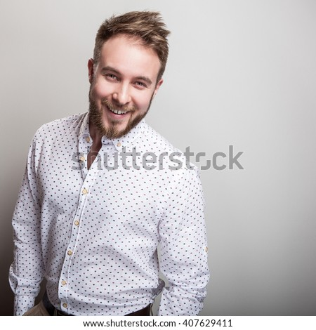 Portrait of young handsome positive man in white shirt with an amusing pattern. - stock photo