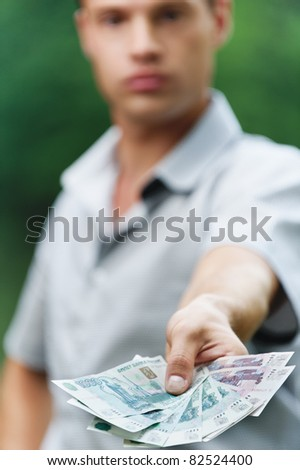 Portrait of young handsome serious man giving money at summer green park. - stock photo
