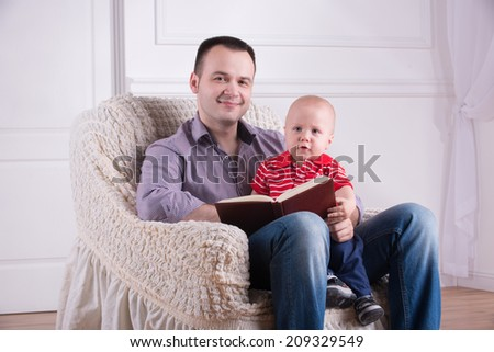 Portrait of young handsome smiling father sitting in cozy armchair holding his toddler son on knees and reading a book, interior shot - stock photo