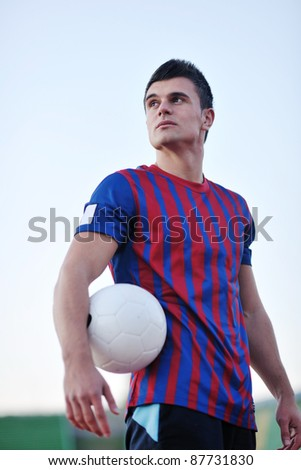 portrait of young handsome soccer player man at football stadium and green grass - stock photo