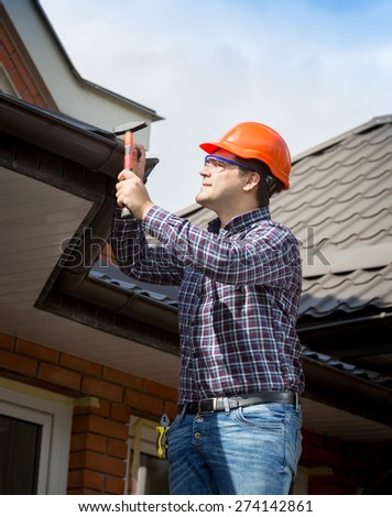 Portrait of young handyman repairing house roof with nails and hammer - stock photo