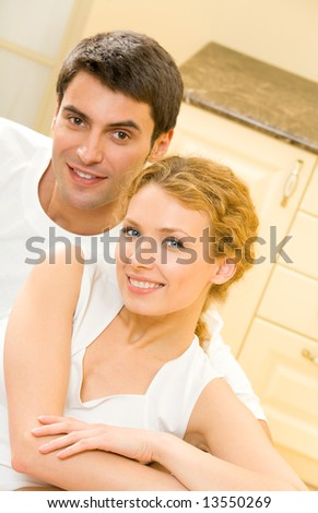 Portrait of young happy amorous couple at home - stock photo