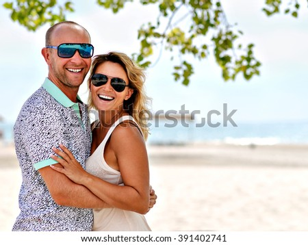 Portrait of young happy attractive couple standing at the sunny beach. - stock photo