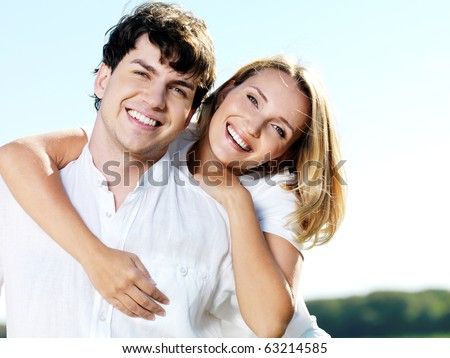portrait of young happy beautiful couple on blue sky background - stock photo