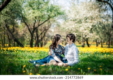 portrait of young happy beautiful couple on nature. love story. They kiss and hug each other. - stock photo