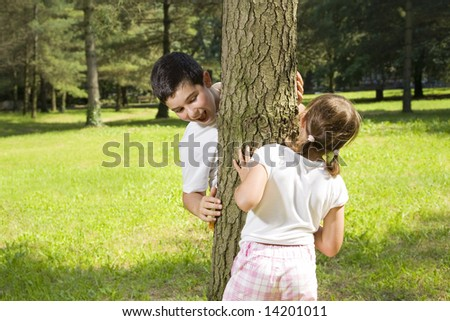 Portrait of young happy boy and girl playing hide and seek at park. - stock photo