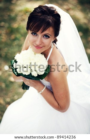 Portrait of young happy bride with flowers