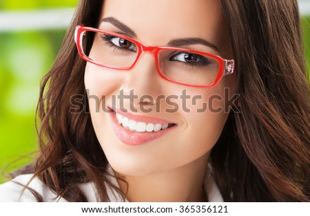 Portrait of young happy brunette businesswoman in glasses