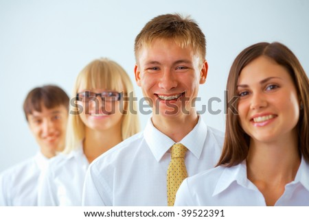 Portrait of young happy business man with his colleagues standing in a row - stock photo