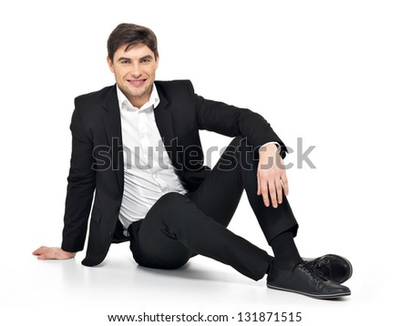 Portrait of young happy businessman  sitting on the floor isolated on white. Concept communication.