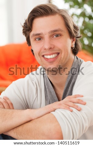Portrait of young happy caucasian man at home