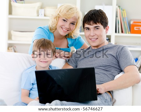 Portrait of young happy cheerful family with son and laptop - indoors - stock photo
