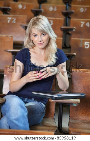 Portrait of young happy college girl sending a text message - stock photo