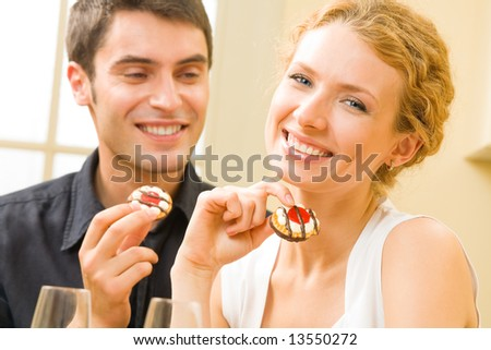 Portrait of young happy couple eating cakes at home - stock photo
