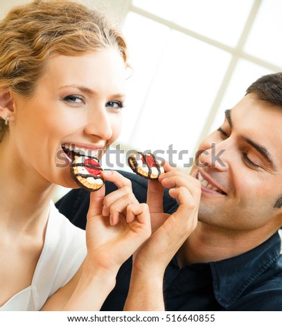 Portrait of young happy couple eating cakes at home. Love, relations, romantic concept shoot.