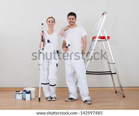 Portrait Of Young Happy Couple Holding Paint Roller
