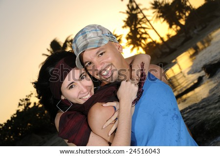 Portrait of young happy couple hugging on tropical beach at sunset - stock photo