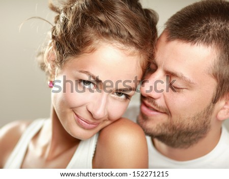 Portrait of young happy couple, isolated on beige background - stock photo