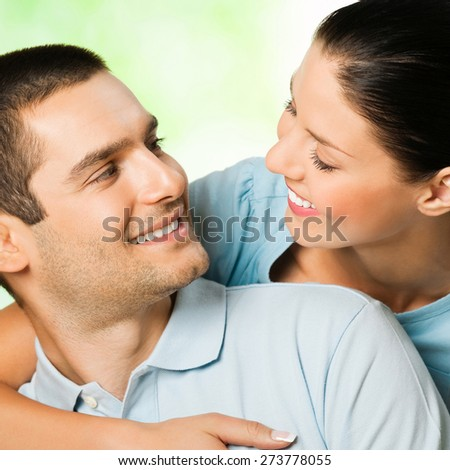 Portrait of young happy couple looking at each other, outdoor - stock photo