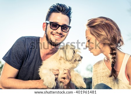 Portrait of young happy couple playing with dog in a park - stock photo