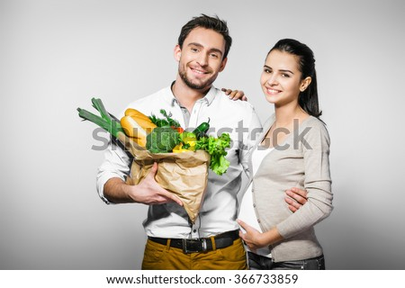 Portrait of young happy couple standing against grey background. Man looking at camera and holding package with fresh vegetables and bread. Man hugging his smiling pregnant wife - stock photo