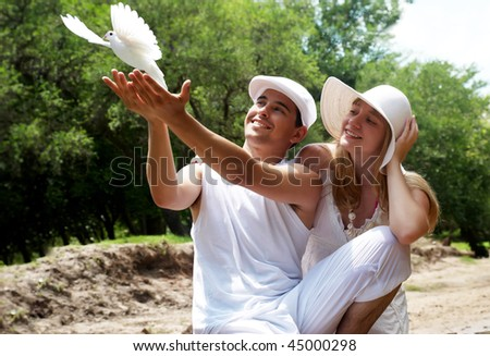Portrait of young, happy couple with dove against the nature - stock photo