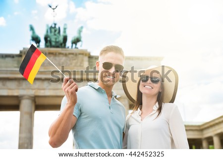 Portrait Of Young Happy Couple With German Flag Standing At Brandenburg Gate - stock photo