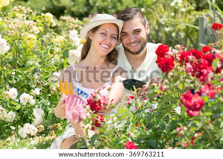 Portrait of young happy couple working in garden of roses at summer day