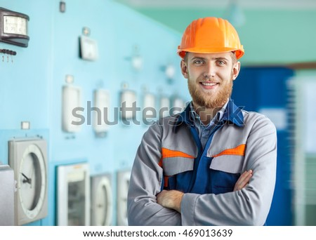 Portrait of young happy engineer at control room. Crossed arms