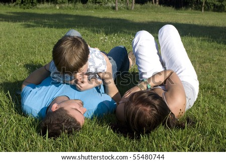 Portrait of young happy family in summer environment - stock photo