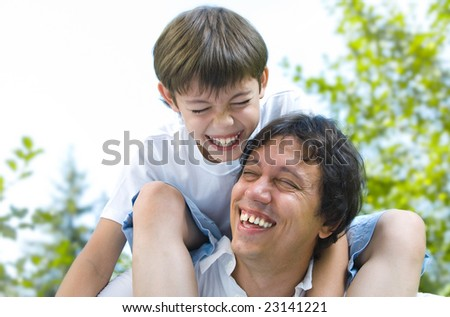Portrait of young happy father getting  busy with his son