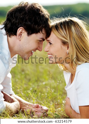 portrait of young happy  flirting couple lying  in green meadow and looking against each other - stock photo