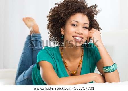 Portrait Of Young Happy Girl Lying On White Couch - stock photo