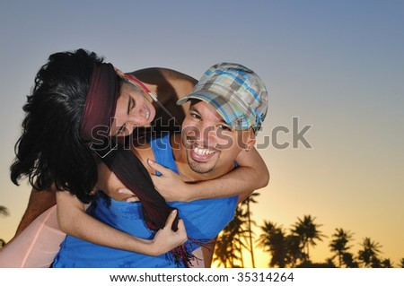 Portrait of young happy hispanic couple embracing on beach background - stock photo