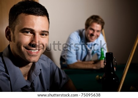 Portrait of young happy man at snooker table, holding cue, having beer, friend smiling in background.? - stock photo