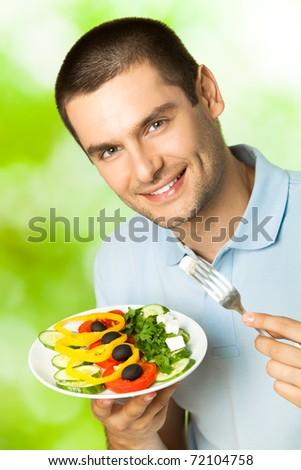 Portrait of young happy man eating salad, outdoors - stock photo