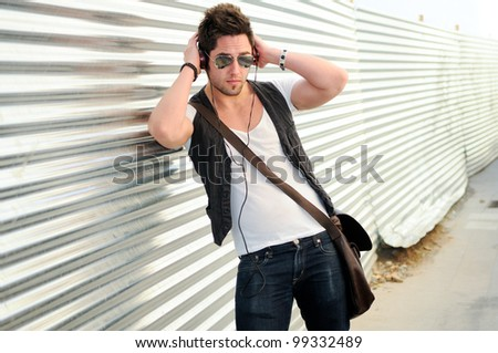 Portrait of young happy man in urban background - stock photo
