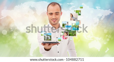 Portrait of young happy man sharing his photo and video files in social media resources using his modern tablet computer. - stock photo