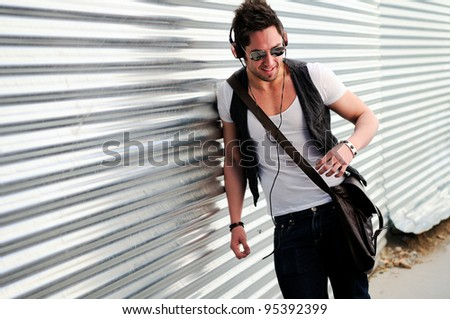 Portrait of young happy man smiling in urban background - stock photo